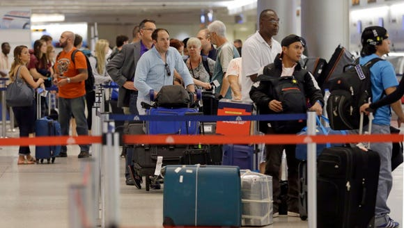 Travelers wait in line to check in their luggage at