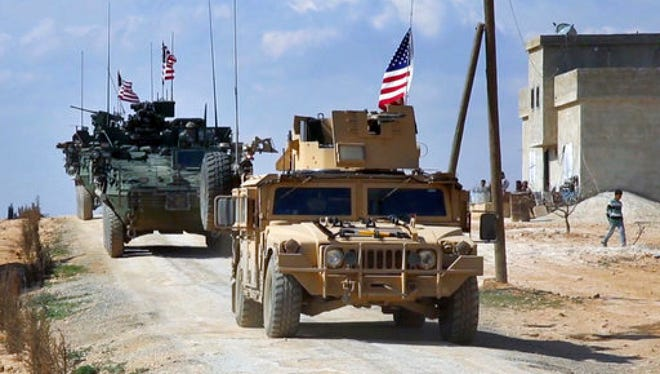 This March 7, 2017, file frame grab from video provided by Arab 24 network, shows U.S. forces patrolling on the outskirts of the Syrian town of Manbij, in Aleppo province, Syria.