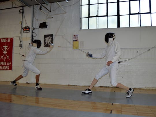 Two fencers practice sparring at the Rockland Fencing