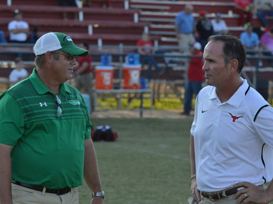 Wall head coach Houston Guy (left) and Eastland head coach James Morton speak prior to their game in 2018.