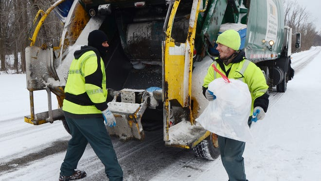 Tony Thompson, left, and Eric Rue collect trash for Waste Management in January 2014. The company would distribute large recycling carts about two years later — a move city officials say is the reason why recycling increased in 2016.