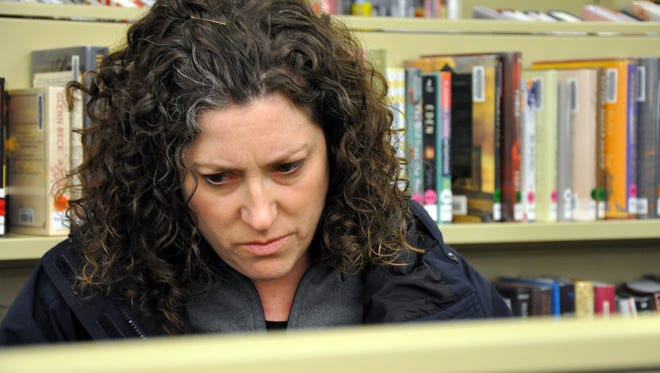 After recognizing an author as a polarizing political commentator, Andrea Barnes, 44, takes a second pick off the shelves at the Cuyahoga Falls Public Library. Barnes prefers civility in politics. Most voters, like her, aren't happy with the divisiveness of presidential elections.