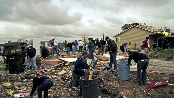 People clean up debris in the aftermath of the tornado that struck Windsor in 2008. Weld County leads the nation in tornadoes, although the majority are too weak to cause major damage.