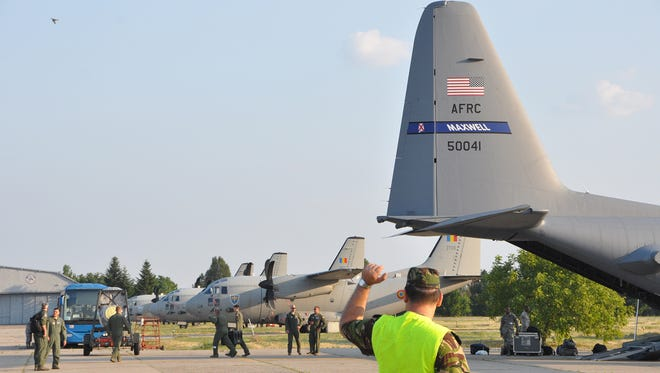Chief Master Sgt. Leon Alexander directs the aircraft to its parking place on arrival at Otopeni Air Base, Romania. Otopeni is located on the outskirts of Bucharest.