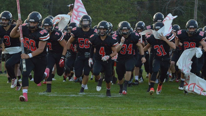 The Pleasant Spartans run onto the field before a home game with Marion Harding this season. The Spartans will celebrate the 45th anniversary of their second football state championship Friday during homecoming and Saturday evening at the all-alumni reunion at the Coliseum.