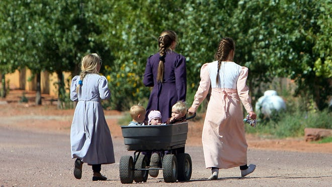 Two women in traditional pioneer FLDS dress pull a wagon of small children across the street with another girl in Colorado City.