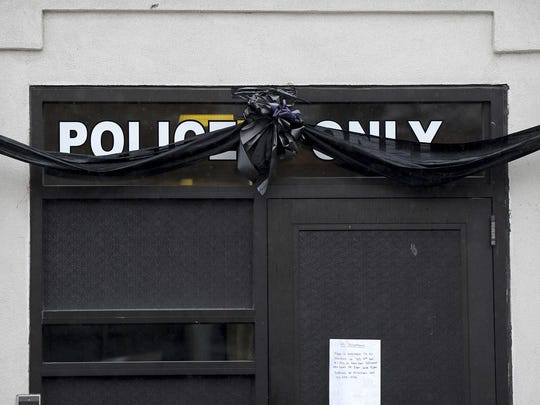 The entrance to the New Kensington Police station is draped in black following the fatal shooting of New Kensington Police Officer Brian Shaw Saturday, Nov. 18, 2017, in New Kensington, Pa. Shaw was shot in the chest Friday night in New Kensington, northeast of Pittsburgh. The shooting occurred during a foot chase that began shortly after the traffic stop took place. (Pam Panchak/Pittsburgh Post-Gazette via AP)