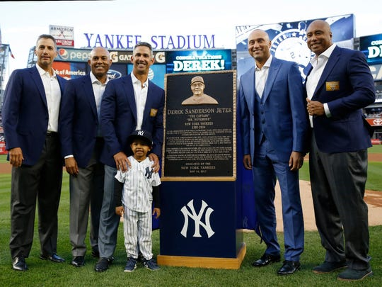 Derek Jeter stands next to his Monument Park plaque following Sunday's ceremony at Yankee Stadium. Jeter joined (from L to R) Andy Pettitte, Mariano Rivera, Jorge Posada and Bernie Williams in having his number retired.