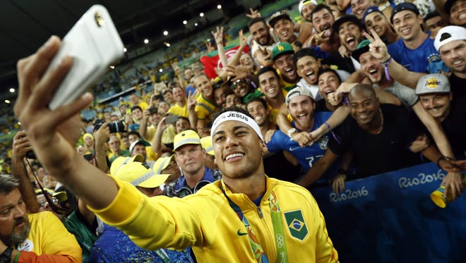 TOPSHOT - Brazil's forward Neymar poses for a selfie with fans as they celebrate after the Rio 2016 Olympic Games men's football gold medal match between Brazil and Germany at the Maracana stadium in Rio de Janeiro on August 20, 2016.  / AFP PHOTO / Odd ANDERSENODD ANDERSEN/AFP/Getty Images ORIG FILE ID: AFP_FG01T