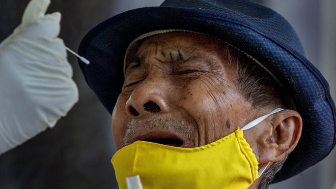 A man grimaces as a nasal swab sample is collected from him to test for a new coronavirus in Bangkok, Thailand, Wednesday, May 6, 2020. Thai health workers started testing community of about 1,600 people of Klong Toey slum at a nearby Buddhist temple.