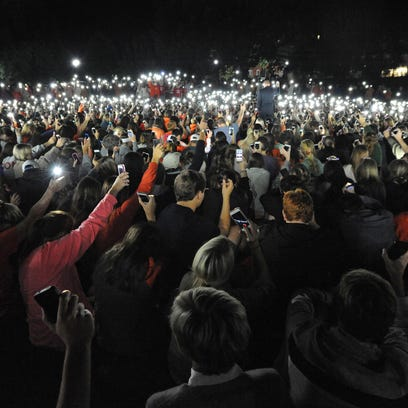 Clemson students hold cell phones during a vigil on