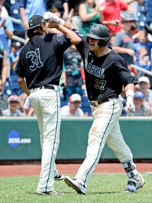 Coastal Carolina Chanticleers designated hitter G.K. Young (37) celebrates with pitcher Bobby Holmes (31) after hitting a two run home run during the sixth inning against the Arizona Wildcats in game three of the College World Series championship series at TD Ameritrade Park.