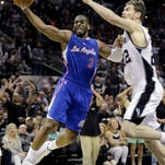 Clippers guard Chris Paul, left, tries to score around Spurs center Tiago Splitter on Sunday in San Antonio.