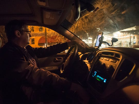 Uber and Lyft driver Scott Saathoff waits for passengers to make their way to his vehicle early Sunday morning, March 11, 2018, in Old Town Fort Collins, Colo.