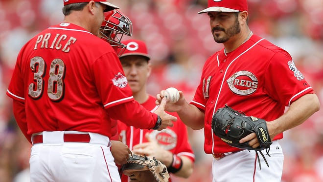 Reds manager Bryan Price, left, pulls starting pitcher Jason Marquis (right) out of the game in the sixth inning Monday against the Rockies.