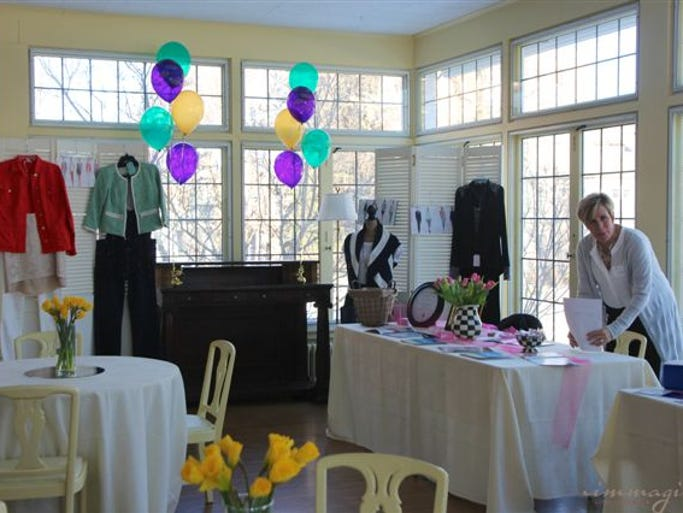 Martha Glickman sets up her CAbi Clothing display at the Women of Focus tradeshow at the Century Club in Rochester on March 6, 2014.