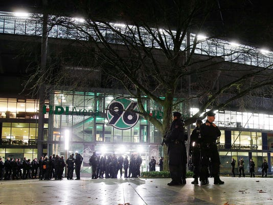 Police officers stand outside the HDI-Arena stadium as the soccer friendly match between Germany and the Netherlands was cancelled in Hannover, Germany, Tuesday, Nov. 17, 2015. (AP Photo/Michael Sohn)