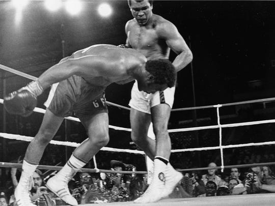 Muhammad Ali watches as defending world champion George
