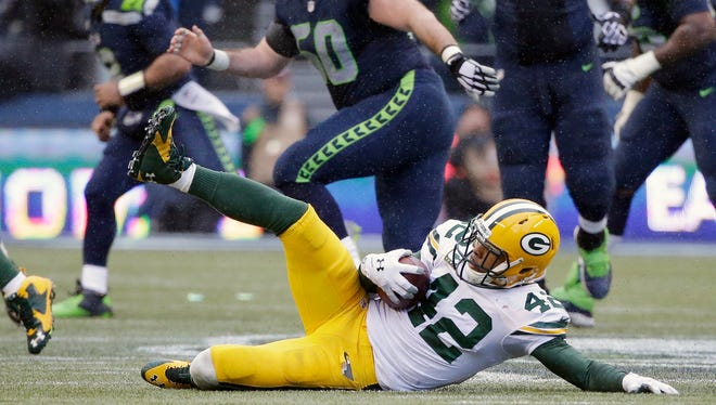 Green Bay Packers safety Morgan Burnett slides after intercepting a pass against the Seattle Seahawks during the fourth quarter of Sunday's NFC championship game at CenturyLink Field in Seattle.