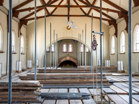 In this June 2, 2017 photo Scaffolding is hung just below ceiling lights, as seen from the choir balcony above the sanctuary at the Church of the Forty Martyrsas major renovation  work gets underway in Tuscola, Ill. Two months from now, parishioners at church will be able to establish a cozy new seating arrangement for weekend Mass. The rest of the week, they can relax in their old pews from the comfort of their own homes. To help pay for its $200,000 renovation, and preserve the most cherished parts of the church, Forty Martyrs (est. 1925) sold the pews being replaced for $250 each.