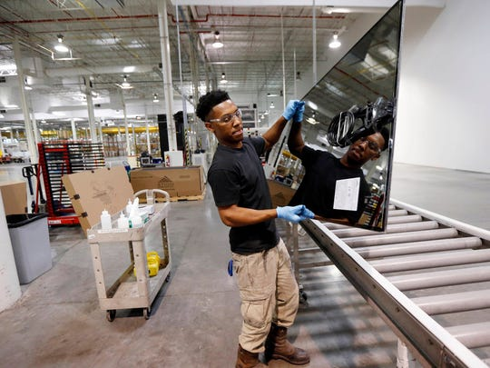 In a 2016, photo, Ricky Foster gingerly carries a completed solar panel to a shipping case after inspecting and cleaning its surface at Stion, a solar panel maker in Hattiesburg, Miss.