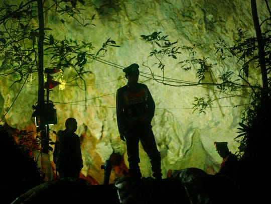 Thai police stand in front of the entrance to a cave