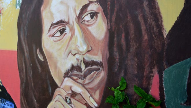 A mural depicting reggae music icon Bob Marley decorates a wall in the yard of Marley's Kingston home in Jamaica.