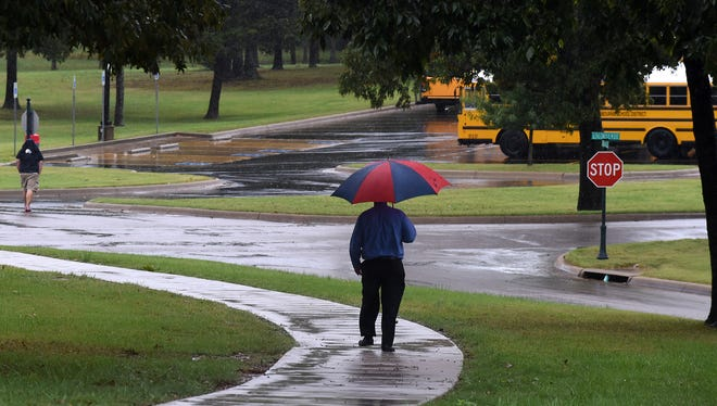 A man tries to stay dry today while walking Friday at Arkansas State University Mountain Home. Rain is forecast throughout the weekend.