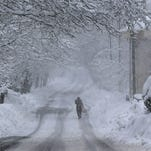 A Lebanese villager walks in the middle of a road covered in snow,  in Sawfar village, mount Lebanon, Friday, Feb. 20, 2015. A heavy winter storm descended on parts of the Middle East of the West Bank, Lebanon, Jordan and Syria as a cold front swept through the region. The Beirut-Damascus highway was closed since late Thursday and the Lebanese fire department urged people to stay at home. (AP Photo/Hussein Malla)