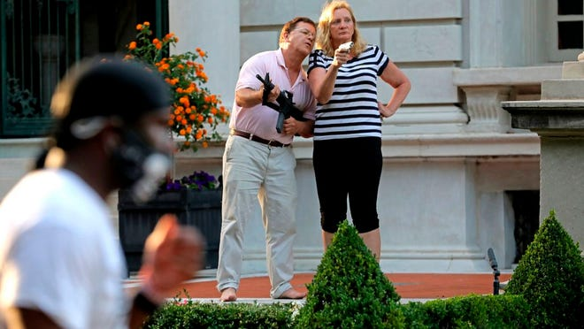 """FILE - In this June 28, 2020 file photo, Mark and Patricia McCloskey emerged from their St. Louis mansion with guns after protesters walked onto their private street. The couple, who were criminally charged for the incident, will make the case in a recorded message Monday night, Aug. 24 in their opening night speech of the Republican National Convention that they had a """"God-given right"""" to defend themselves and their property."""