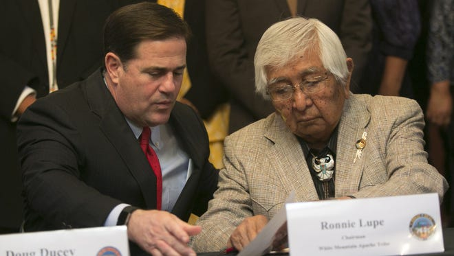 Gov. Doug Ducey (left) and White Mountain Apache Chairman Ronnie Lupe sign a deal to renegotiate tribal gaming compacts.