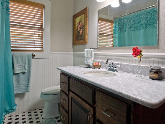 The hall bath has bead board wainscoting, a cool marble