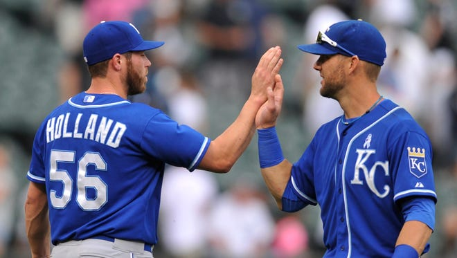 Kansas City Royals closing pitcher Greg Holland (56) celebrates with teammate Alex Gordon right, after defeating the Chicago White Sox 6-3 in a baseball game in Chicago, Sunday, June 15, 2014.