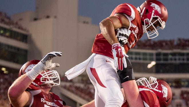 Arkansas Razorbacks offensive tackle Frank Ragnow lifts wide receiver Jared Cornelius after Cornelius scored.