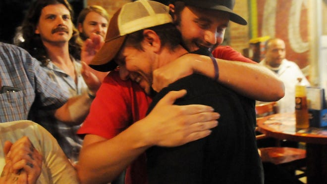 Gary Moore and Ben Kitterlin, right, celebrate as they learn Friday evening at Twisted Root in Shreveport that they are among the five finalists for the Louisiana Music Prize.