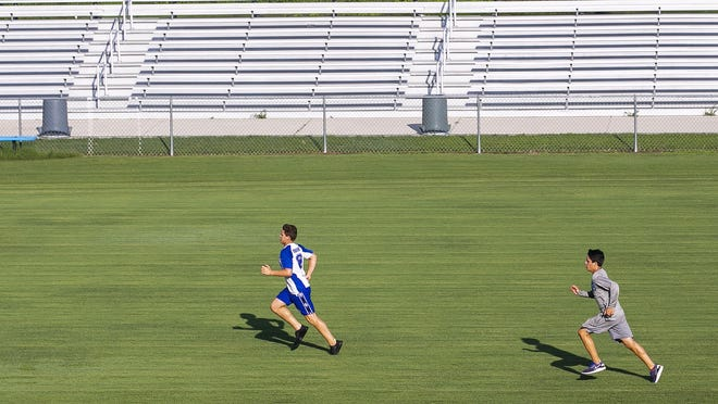 Belleview High School's Eric McLaughlin, left, and his twin brother, Zachary, run 100-yard wind sprints in summer 2019. School campuses can be used for outdoor practice in small groups, beginning Wednesday.