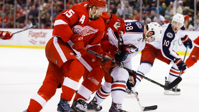 Detroit Red Wings defenseman Niklas Kronwall (55) defenseman Jonathan Ericsson (52) and Columbus Blue Jackets center Boone Jenner (38) battle for the puck in the second period at Joe Louis Arena.