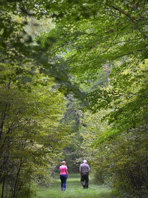 Jenny Kutter, left, department coordinator for St. John's Outdoor University, and Tom Kroll, forester at the St. John's Abbey Arboretum, walk Sept. 16 along the old St. Joe Road Trail that's part of the arboretum.