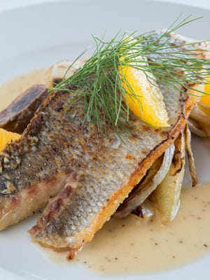 Branzino, a European sea bass, is sautéed and served with fennel and orange supremes atop tender roasted potatoes. It is drizzled with a creamy white wine lemon sauce.