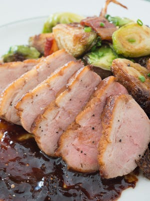 Roux's seared duck breast is served with browned Brussels sprouts with bacon bits, plus an apple and fig gastrique.