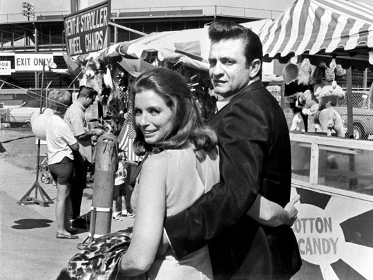 Johnny Cash, with his wife June Carter Cash, stroll the midway at the Mid-South Fair in Memphis, Tenn., in the fall of 1968, a few months after the couple married.