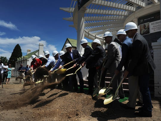 Developers and local dignitaries shovel dirt during