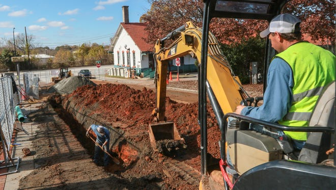 John Finley, right, of Glenn Mechanical in Anderson uses an escavator while Kevin Ward digs in a trench on Federal Street in Anderson. New sewer lines will be going in as business increases on the road.