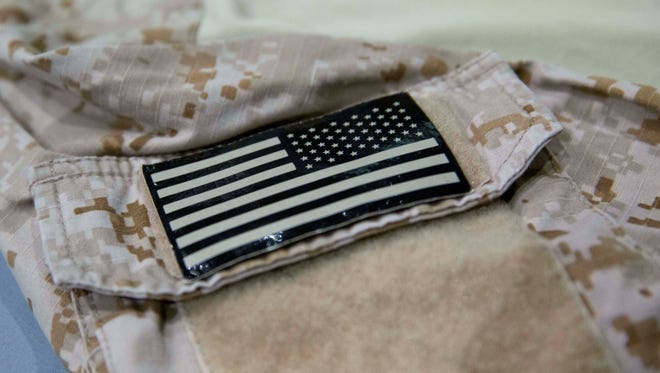 In this Sept. 5 photo provided by the National September 11 Memorial and Museum, a detail of the fatigue shirt showing an American flag emblem worn by the U.S. Navy SEAL during the mission to capture Osama bin Laden is seen in a case at the museum in New York. The shirt and other items from the raid will be introduced to the public today.