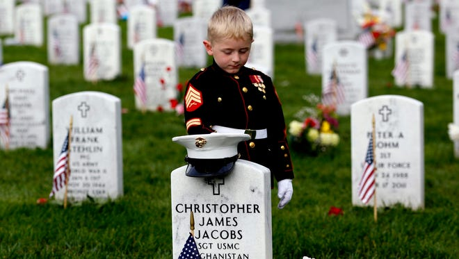 Christian Jacobs, 5, of Hertford, N.C., dressed as a Marine, pauses at his father's gravestone on Memorial Day at Arlington National Cemetery in Arlington, Va. Christian's father, Marine Sgt. Christopher James Jacobs, died in a training accident in 2011.