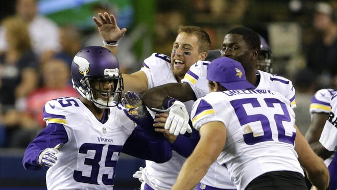 Minnesota Vikings cornerback Marcus Sherels, left, is greeted by teammates, including outside linebacker Chad Greenway (52). after Sherels intercepted a pass from Seattle Seahawks quarterback Trevone Boykin to score the go-ahead touchdown in a preseason game on Aug. 18 in Seattle. The Vikings won 18-11.