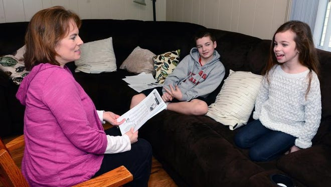 Dawn Young (left) goes over spelling words with son Brian (left) and daughter Kiera.