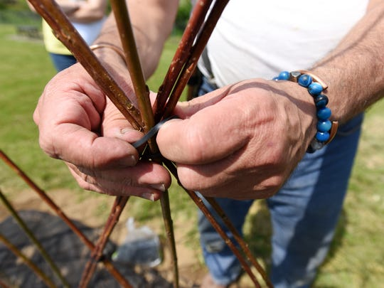 Howard Peller fastens willows together to form part of the living play area at Restoration Park in Zanesville.