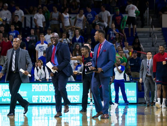 The Florida Atlantic University coaching staff storms the FGCU court with 0.7 seconds left in the game at Alico Arena on Tuesday in the Owls' 92-88 victory.