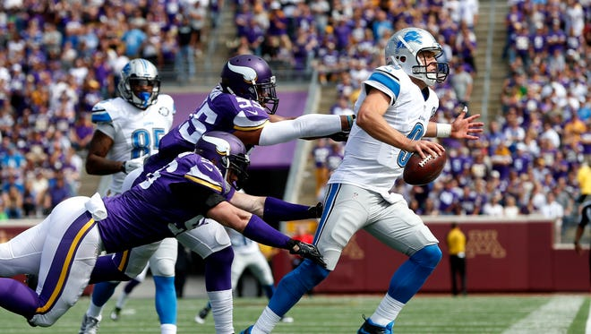 Lions quarterback Matthew Stafford is pushed out of bounds by Vikings defensive end Brian Robison (96) and linebacker Anthony Barr (55) in the second half in Minneapolis in 2015.